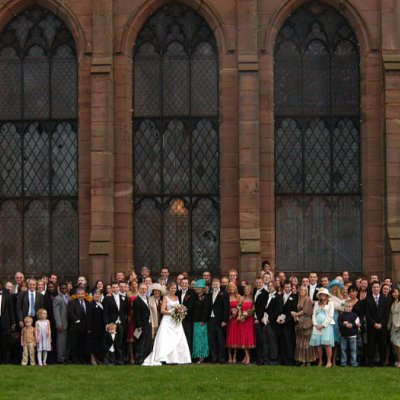 photograph of a large group of people in front of a church at a wedding